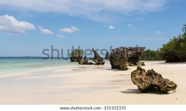Pristine white tropical beach with rocks, blue sea and lush vegetation on the African Island of Misali, Pemba, Zanzibar.