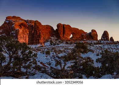 Pristine winter sunset view of Skyline Arch with snow in Arches National Park in Moab, Utah USA