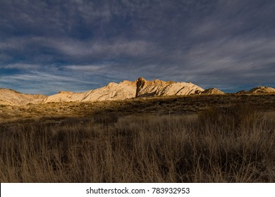 Pristinely illuminated white Navajo sandstone mountain during sunrise in a stormy day in Snow Canyon State Park in Utah.