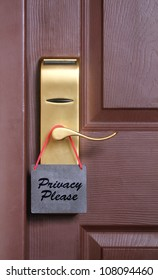 Privacy please words, a common request for others not to disturb the motel or resort room occupants, on a paper cardboard tag hung on the door knob of a hotel