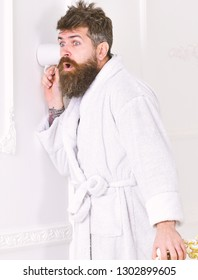 Privacy and secret concept. Man with beard and mustache eavesdrops using cup near wall. Hipster in bathrobe on surprised face secretly listen conversation. Man in white interior spying, eavesdropping.