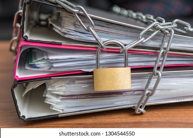 Privacy and security concept. Confidential files and documents in binder locked with padlock and chain.