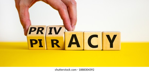 Privacy vs piracy symbol. Businessman hand turns cubes and changes the word 'piracy' to 'privacy'. Beautiful yellow table, white background, copy space. Business and privacy vs piracy concept.