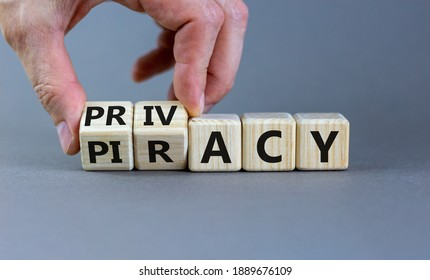 Privacy vs piracy symbol. Businessman hand turns cubes and changes the word 'piracy' to 'privacy'. Beautiful grey background, copy space. Business and privacy vs piracy concept.