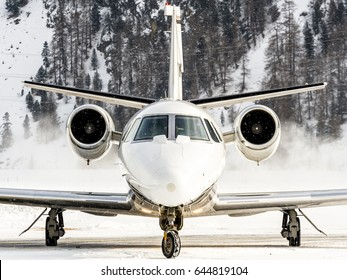 Private aircraft just landed. Frontal shot over snow during taxiing to parking. Bizjet, airplane for VIP and luxury. Reflection on the fuselage made by snow.