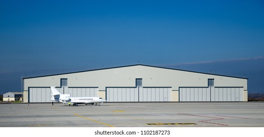 Private aviation. Hangar and a small plane on concrete.