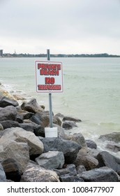 Private Beach sign posted on a rocky beach on the Gulf of Mexico at St. Pete Beach, Florida.