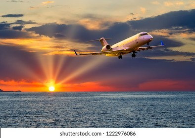 private business jet plane flying over the sea at sunset, the sun's rays cut through the clouds