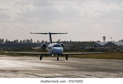 private business jet taxiing on the runway of a small airport