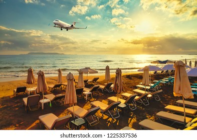 private business plane on landing flies over the sandy beach with sun loungers on the background of sunset, sun and clouds. Crete, Europe