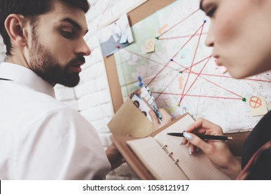 Private detective agency. Man in tie and woman in jacket are looking at map, discussing clues.
