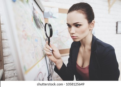 Private detective agency. Woman in jacket is looking at clue map with magnifying glass in office.