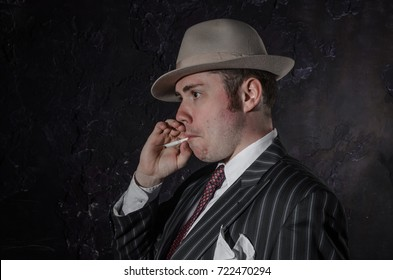 Private detective in old fashion hat smokes a cigarette. Gangster looks like mafiosi and stay side to camera. He wears a mob jacket. Police criminal scene in black and white. Studio shot.