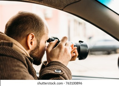 Private detective or reporter or paparazzi sitting in car and taking photo with professional camera, toned