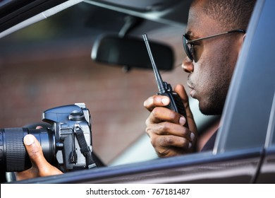 Private Detective Sitting Inside Car Holding SLR Camera And Walkie Talkie