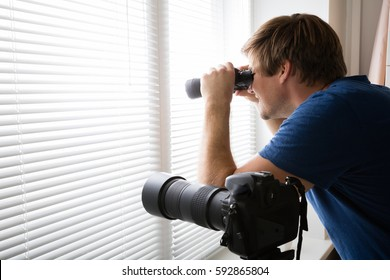 Private Detective Spying With Binoculars Looking Through Blinds Near SLR Camera