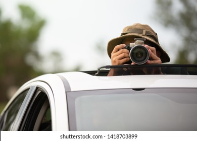 Private detective spying with camera looking through sunroof  of a car.