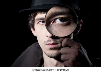 Private detective watching through a magnifying glass, isolated on a black background