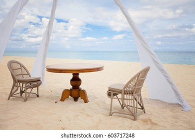 Private dining table and wicker chairs for romantic dinner for honeymoon couples on a tropical beach