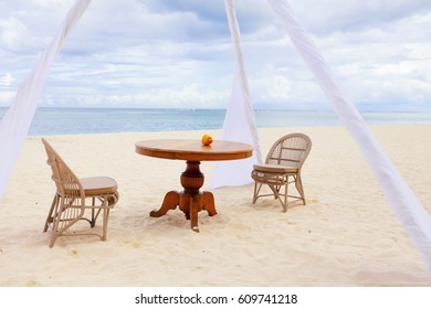 Private dining table and wicker chairs for romantic dinner for honeymoon  couples on a tropical beach of Mauritius
