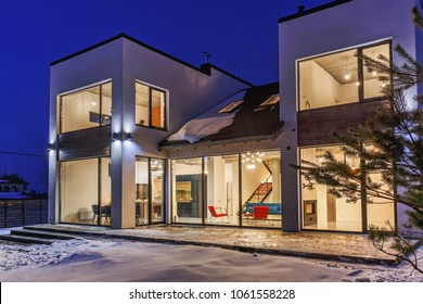 private house with panoramic windows in a modern style on a background of the night sky.