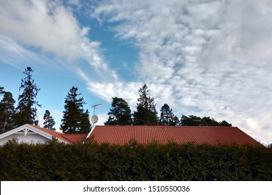 Private house roof with red tiles over green bushes with blue sky over.