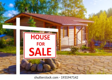 Private house for sale. House for sale sign on the background of a blurry image of a cottage. Buying and selling real estate. Rural properties. Sale of houses in rural areas.