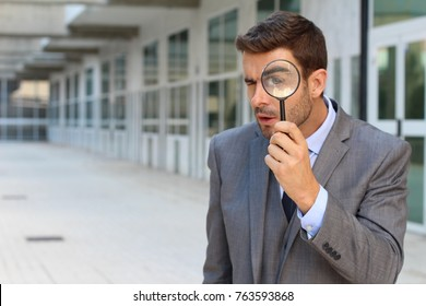 Private investigator looking through a magnifying glass