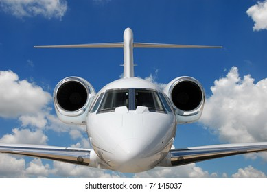 Private jet against blue sky and clouds