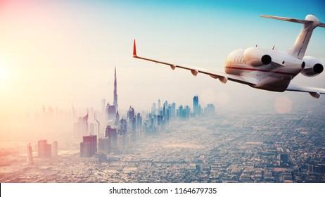 Soukromé tryskové letadlo létající nad městem Dubaj v krásném světle západu slunce. Moderní a nejrychlejší způsob dopravy, obchodní život.