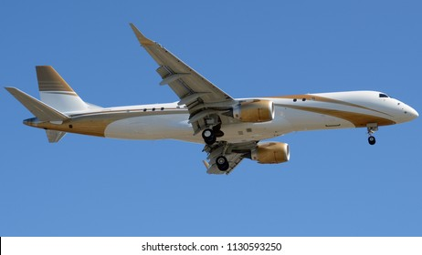 A Private Jet with Wavy Gold Paint Flying with its Landing Gear Down