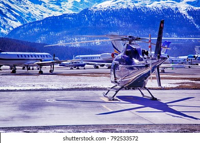 Private jets, planes and helicopters in the beautiful snow covered mountains of alps in St Moritz Switzerland