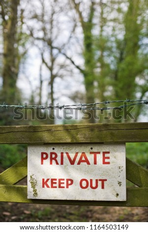 """Private Keep Out"" sign on a gate in a woodland."