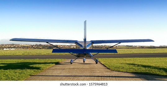 A private light airplane sits on the apron of a small airfield. Ready for flight beside the taxi way. Blue fuselage, wings, tail . Also refererred to as a microlight, ultralight, or light sports plane