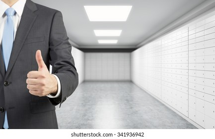 A private manger of a bank with thumb up stands in a room with safe deposit boxes. A concept of storing of important documents or valuables in a safe and secure environment.
