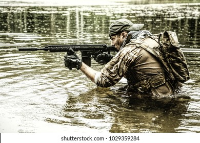 Private military contractor PMC in baseball cap during river raid in the jungle waist deep in the water and mud