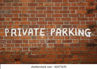 Private parking sign painted on red brick wall