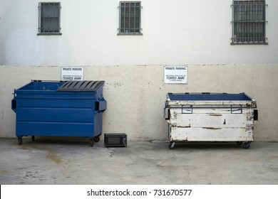 private parking signs above two commercial trash containers