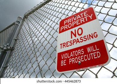Private Property No Trespassing Violators Will Be Prosecuted Red and White Sign on Chain Link Fence on a Cloudy Afternoon