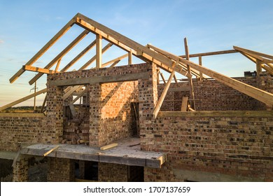 Private residential house with wooden roof frame structure under construction. Unfinished brick building under development.
