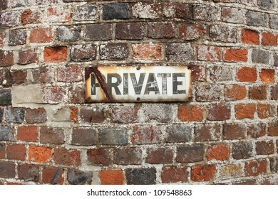 Private sign on an old brick wall