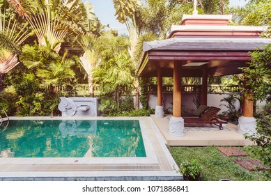 Private swimming pool with alcove, sunbeds and exotic palm trees near luxury villa
