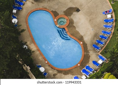 private swimming pool in residential area suburb house aerial view from the top surrounded by green garden and foldable chairs furniture