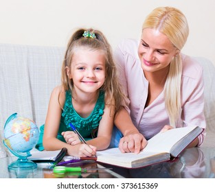 Private teacher and little girl studying and writing at home