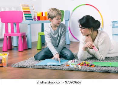 Private teacher and small boy learning by play at home