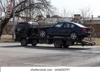 Private towing vehicle for emergency vehicle movement. Passenger car after an accident on a forklift truck on the road in motion
