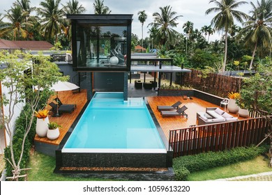 Private tropical swimming pool and gym near luxury villa. Sunny summer travel vacation, palm trees jungle