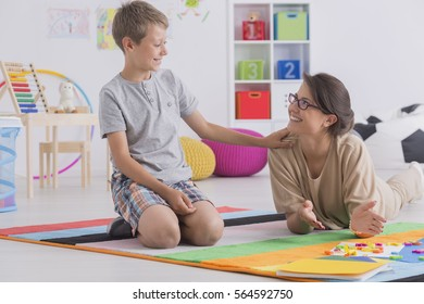 Private tutor and happy child studying in light interior