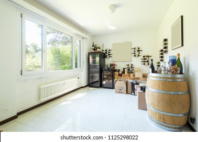 Private wine cellar with many wines, boxes and wooden barrels. Nobody inside