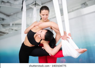Private yoga class. Young active woman in black leggings and top coming to private aerial yoga class